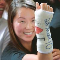 Healthy approach: A woman holds up her cast after U.S. President Barack Obama wrote the words 'I (heart) Obamacare' on it in Boston on Oct. 3. | AFP-JIJI