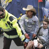 Run to safety: An emergency responder and volunteers, including Costa Rican-American peace activist and Red Cross volunteer Carlos Arredondo (center), push victim Jeff Bauman in a wheelchair after he was wounded by the Boston Marathon bombings on April 15. | AP