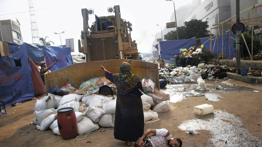 Full stop: An Egyptian woman tries to prevent a military bulldozer from hurting an injured youth during action against supporters of deposed President Mohammed Morsi at a protesters' camp in Cairo on Aug. 14. | AFP-JIJI