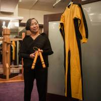 On the block: Spink auction house Vice Chairman Anna Lee with the jumpsuit worn by Bruce Lee during the filming of 'Game of Death' in 1972. | AFP-JIJI