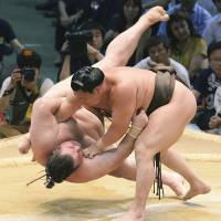 King of the castle: Hakuho throws Gagamaru to the ground at the Nagoya Grand Sumo Tournament in July.    KYODO