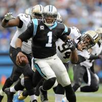 People are chasing you: Panthers quarterback Cam Newton runs from Saints defenders during Carolina's 17-13 win over New Orleans on Sunday in Charlotte, North Carolina. | AP