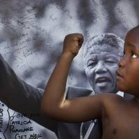 Strength through struggle: A member of the Maitibolo Cultural Troupe poses in front of a placard of Nelson Mandela outside the entrance to the Pretoria hospital where the former South African president was being treated in July before his death. | AP