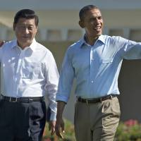 World powers: Chinese President Xi Jinping and U.S. leader Barack Obama wave as they walk at the Sunnylands estate in Rancho Mirage, California, during a June summit. | AP