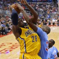 Let's get physical: Pacers center Ian Mahinmi (left) gets his shot blocked by the Clippers' Antawn Jamison on Sunday in Los Angeles. The Pacers won 105-100. | AP
