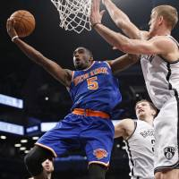 Take it to the rack: Tim Hardaway Jr. (left) goes up for a layup against Nets forward Mason Plumlee on Thursday. | AP