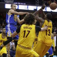 You got me: Warriors guard Stephen Curry makes a pass as the Cavaliers defend on Sunday in Cleveland. | AP