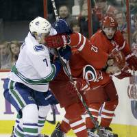 Got your nose: The Hurricanes' Eric Staal (right) competes for the puck against the Canucks' David Booth on Sunday.   AP