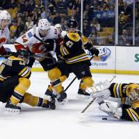 Just in time: Boston's Tuukka Rask falls on the puck in the third period against Calgary on Tuesday night. The Bruins won 2-0. | AP