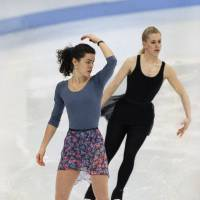 A pair forever linked: Nancy Kerrigan (foreground) and Tonya Harding skate during a practice session at Hamar Olympic Amphitheater, in Hamar, Norway, in a Feb 22, 1994, file photo. | AP
