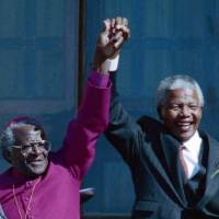 Two of a kind: Former South African President Nelson Mandela (right) holds hands with former Bishop Desmond Tutu in Cape Town in 1994. | AP