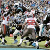Up, up, and away: Panthers quarterback Cam Newton dives over the pile to score against the Buccaneers on Sunday. Carolina won 27-6.  | AP
