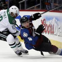 Falling down: Colorado's Tyson Barrie slides into the boards as Dallas' Ray Whitney looks on in the third period on Monday night.   AP