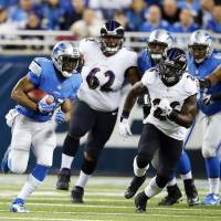 Kicking it in gear: Baltimore Ravens defenders chase Detroit's Reggie Bush during the first quarter on Monday night. | AP