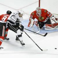 Tag team: Los Angeles' Jordan Nolan moves for his own rebound as Chicago's Nick Leddy (left) and Antti Raata defend on Monday.   AP