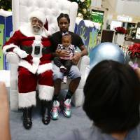 Dreaming of a multicolored Christmas: Dressed as Santa Claus, Langston Patterson (left) poses with Davonte Hager and his daughter Maliyaah, 1, at Baldwin Hills Crenshaw Plaza mall in Los Angeles. | AP