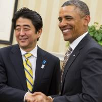 Prime Minister Shinzo Abe and U.S. President Barack Obama shake hands at the White House in Washington, D.C., in February 2013.  | BLOOMBERG