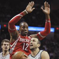 Blanket defense: San Antonio's Manu Ginobili goes up for a shot against Houston's Dwight Howard in the first half on Saturday night. The Rockets downed the Spurs 112-106. | AP