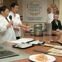 Motokazu Nakamura (left), master chef at Japanese restaurant Nakamura Kyoto Cuisine, speaks about the umami taste during a seminar at the Culinary Institute of America, a cooking school in New York, on Feb. 4, 2013. | COURTESY OF UMAMI INFORMATION CENTER/KYODO