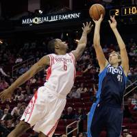 High arc: Dallas' Dirk Nowitzki launches a jumper over Houston's Terrence Jones in the first half on Monday night. | AP