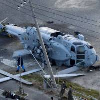 Black Hawk down: A U.S. Navy helicopter lays on its side at a landfill near Misaki Port in Miura, Kanagawa Prefecture, after making an emergency landing that injured two of its four crew members. | KYODO