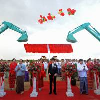 Building for the future: People involved in a joint Myanmar-Japan project to create a special economic zone hold a ribbon-cutting ceremony Saturday in Thilawa in the outskirts of Yangon. A total of 2,400 hectares of land will be developed for the zone. | AFP-JIJI