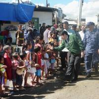Reality check: Defense Minister Itsunori Onodera is greeted by children at an evacuation facility in the Philippine city of Tacloban, which was heavily damaged by Typhoon Haiyan. Onodera was on a two-day visit that started Saturday. | KYODO