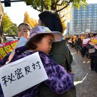 Family affair: A mother holds her sleeping daughter with a sign reading 'anti-secrets' during a rally against the state secrecy bill in front of the Diet on Thursday. | AFP-JIJI