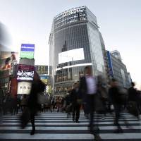 Cooperative convergence: Pedestrians cross the main intersection in front of JR Shibuya Station in Tokyo on Nov. 22. | BLOOMBERG