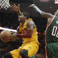 Eyes on the prize: Cavaliers guard Kyrie Irving attempts to get a shot off against the Bucks' O.J. Mayo. | AP
