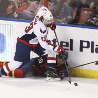 On-ice clash: The Capitals' Jay Beagle and the Panthers' Aleksander Barkov fight for the puck in third-period action on Friday. | AP