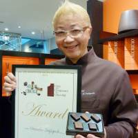 Candy man: Hironobu Tsujiguchi, at one of his shops in Shibuya Ward, Tokyo, shows off the top award from the Salon du Chocolat global chocolate fair in Paris, which he received in November. | KYODO