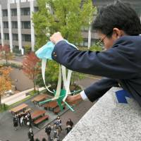 Handle carefully: A student drops an egg in a protector at the Egg Drop Koshien contest in Kyoto on Nov. 3. | KYODO
