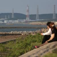 Standing idle: A couple look toward Tokyo Electric Power Co.'s offline Kashiwazaki-Kariwa nuclear plant in Niigata Prefecture in September. Although some new renewable energy projects are set to come online, Japan's energy situation in 2014 mostly hinges on restarts of idled reactors. | BLOOMBERG