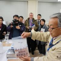 Beyond the Geiger counter: A researcher at Marine Ecology Research Institute in Onjuku, Chiba Prefecture, explains to foreign journalists how a fish sample is prepared for a radiation test.   KAZUAKI NAGATA