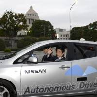 In the hands of technology: Prime Minister Shinzo Abe waves during a test ride in a Nissan automobile equipped with an automated driving system near the Diet building last month. | KYODO