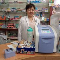 One of the store's pharmacists, Akiko Nagai, gives an explanation about the simple diabetes test while standing next to a device designed to measure glycated hemoglobin in blood. | MAMI MARUKO