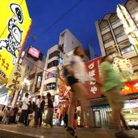 Evolving: People walk through Osaka's lively Dotonbori district one night in June 2012. Osaka is attempting to attract more foreign tourists by turning it into an entertainment destination. | BLOOMBERG