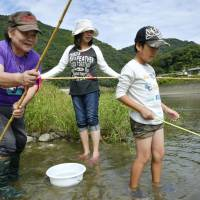 Environmentalist: Shoko Tsuru (left), who has spearheaded a campaign to remove dams from the Kuma River in Kumamoto Prefecture, takes part in a fishing event. | KYODO