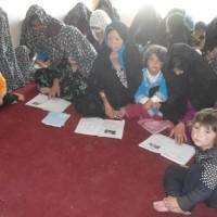 Fundamentals: Afghan women, including mothers with children, participate in a reading class organized by NICCO as part of the group's support program to build self-reliance. | NICCO