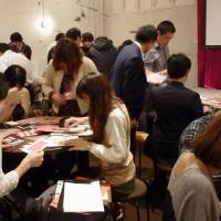 Get a clue: People playing an escape game organized by SCRAP Co. are caught up in trying to figure out puzzles in Shibuya Ward, Tokyo, on Friday. | KYODO