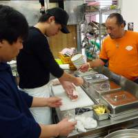 All about broth: A ramen restaurant owner (right) teaches trainees how to prepare barbecued pork at a workshop organized by Shokuno Dojyo Co. | KYODO