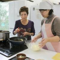 Healthy living: Participants learn how to cook low-calorie, low-sodium meals during a lesson at the National Cancer Center Hospital East in Kashiwa, Chiba Prefecture. | KYODO