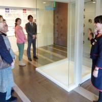Temporary refuge: An employee of Daiwa House Industry Co. explains about the small emergency rooms installed in each of the firm's new apartment buildings. | KYODO