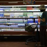 Dairy dilemma: A woman looks over various brands of milk at a supermarket in Urayasu, Chiba Prefecture, in August. | BLOOMBERG