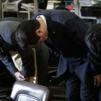 Assume the position: Yasuhiro Sato, president and chief executive officer of Mizuho Financial Group Inc. (center), bows at the start of a news conference in Tokyo on Oct. 28. Sato apologized for the bank's failure to address problems of lending to crime groups. | BLOOMBERG