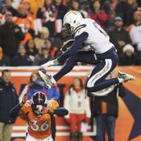 Take the high road: Chargers receiver Keenan Allen leaps over the Broncos' Kayvon Webster during San Diego's upset of Denver on Thursday.   AP