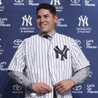 Tailor made: Jacoby Ellsbury slips into a Yankees uniform during his introductory news conference on Friday in New York.   AP