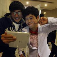 Modern life: North Korean defector Han Jin-beom (right) poses with South Korean friend Kim Min-sung for a photo using a tablet after the concert 'With Friend' in Seoul on Nov. 9. | AP