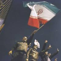 Rah for Rouhani: Waving the flag and holding a poster of President Hassan Rouhani, Iranians welcome nuclear negotiators home from Geneva at the airport in Tehran on Nov. 24. | AP